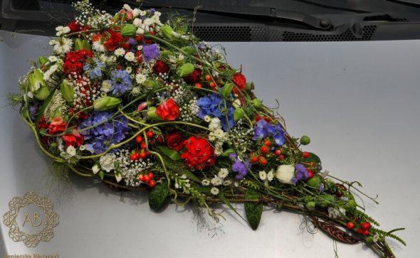 Dekoracja samochodu podłużna kompozycja z białych czerwonych i niebieskich kwiatów