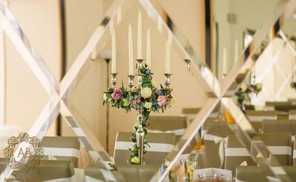 Dekoracja sali na wesele u Ziyada Kraków srebrne kandelabry z wiankami z kremowych zielonych i niebieskich kwiatów i liści Agnieszka Błaszczyk abkwiaty