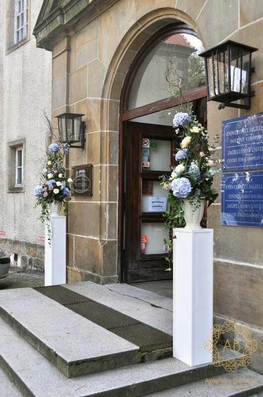 Dekoracja wejścia do Ziyada kompozycje kwiatowe na podestach błękitne hortensje kremowe róże lila ostróżki Agnieszka Błaszczyk abkwiaty