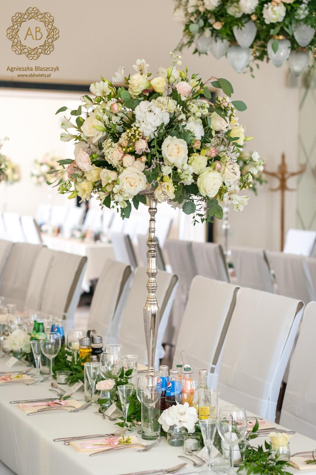Wysoka dekoracja z pastelowych kwiatów na stole weselnym oraz girlanda i świece. ABKwiaty Kraków