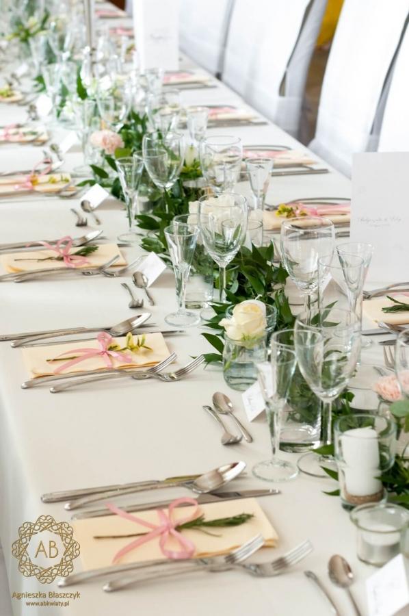 Girlanda z zieleni i punktowo umieszczonych kwiatów na stołach gości. ABKwiaty Kraków